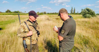 Учасник рейдової групи перевіряє документи у мисливця