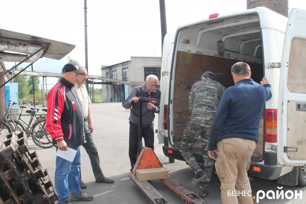 Працівники заводу вантажать товар